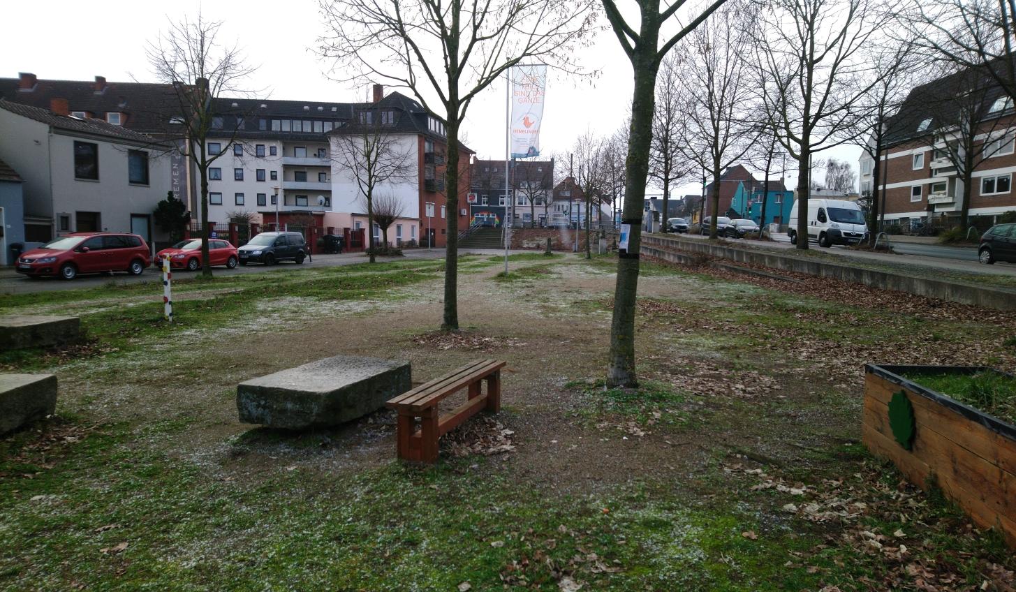 Ein Platz mit Bäumen und Bänken darauf. Der Boden ist teils sandig, teils mit Gras bedeckt.