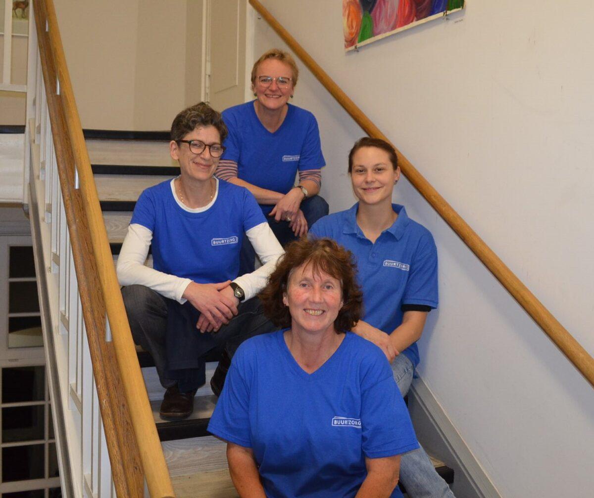 Vier Pflegerinnen von Buurtzorg sitzen auf einer Treppe.