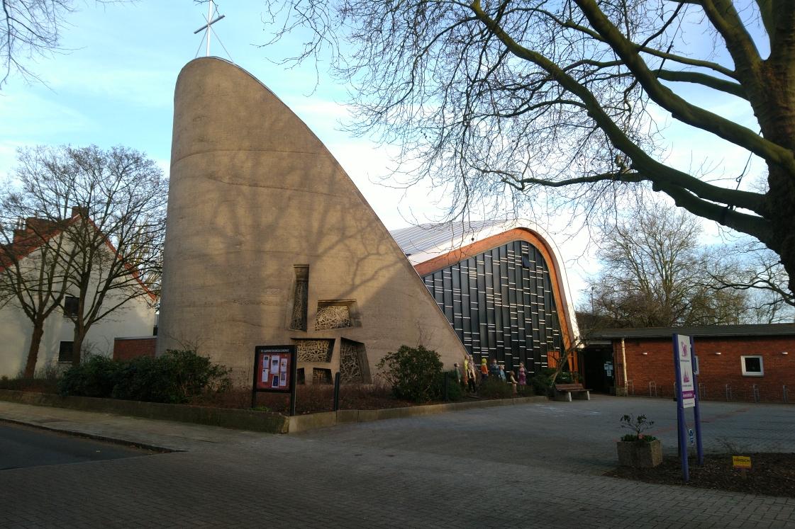 Ein Kirchengebäude aus den 1950er-Jahren. Moderne Architektur, kein klassischer Kirchturm. Das Gebäude erinnert an einen übergroßen Sessel.