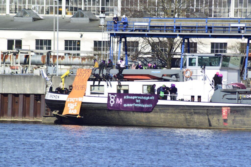Demonstrierende Menschen auf einem Binnenschiff. An dessen Außenwand wurden Plakate befestigt. Auf einem Plakat steht: »Klimagerechtigkeit ist queerfeministisch«.