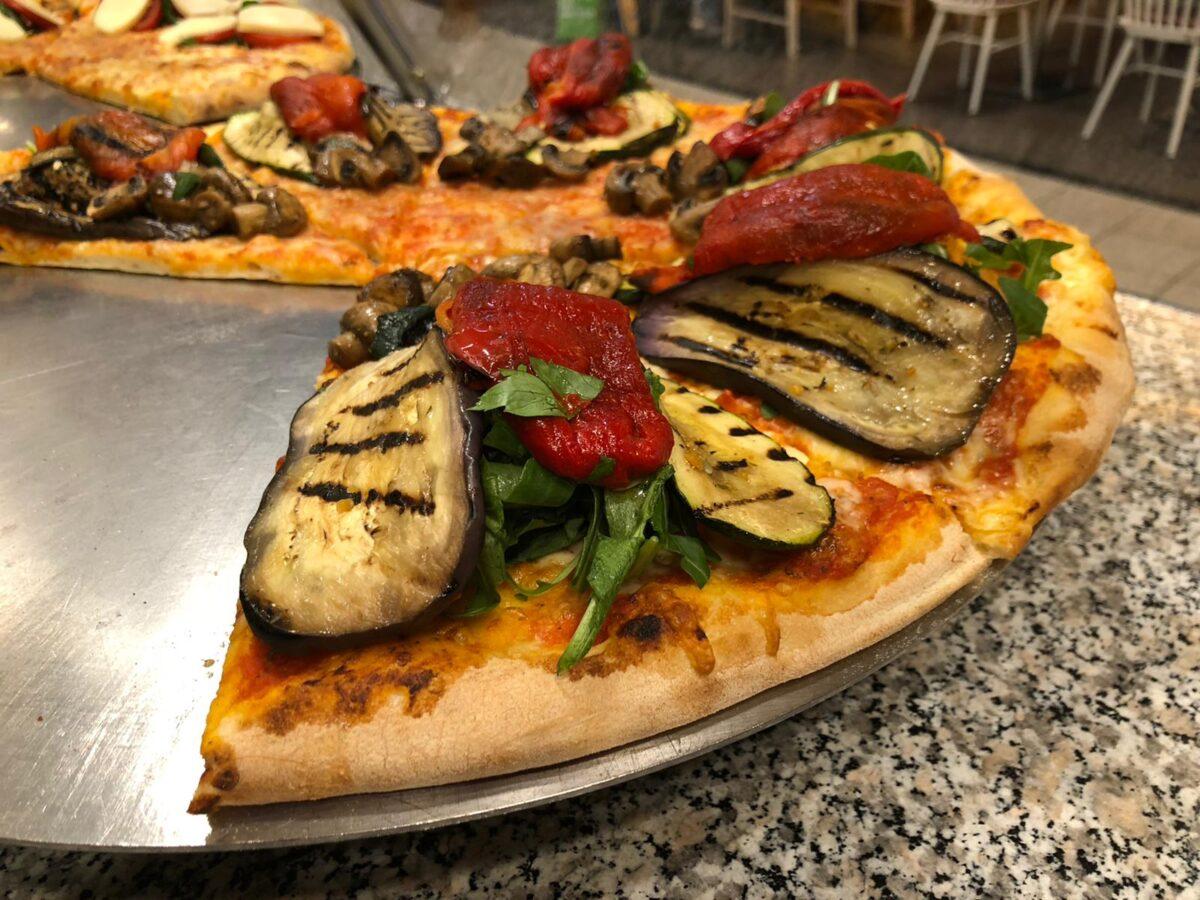 Einige Stücke Pizza, hoch mit gegrilltem Gemüse belegt.