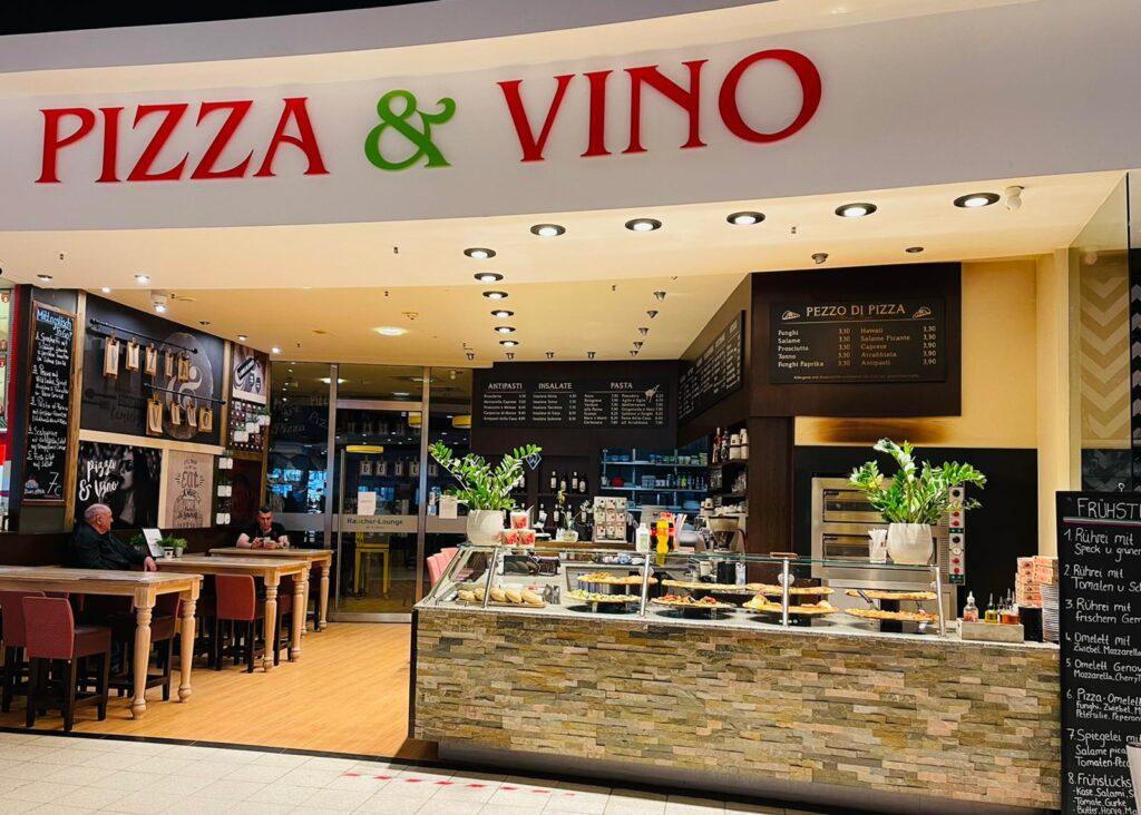 Außenansicht eines italienischen Restaurants. Links Tische, hinten ein Raucherraum, rechts der Tresen mit großen Pizzen im Schaukasten.