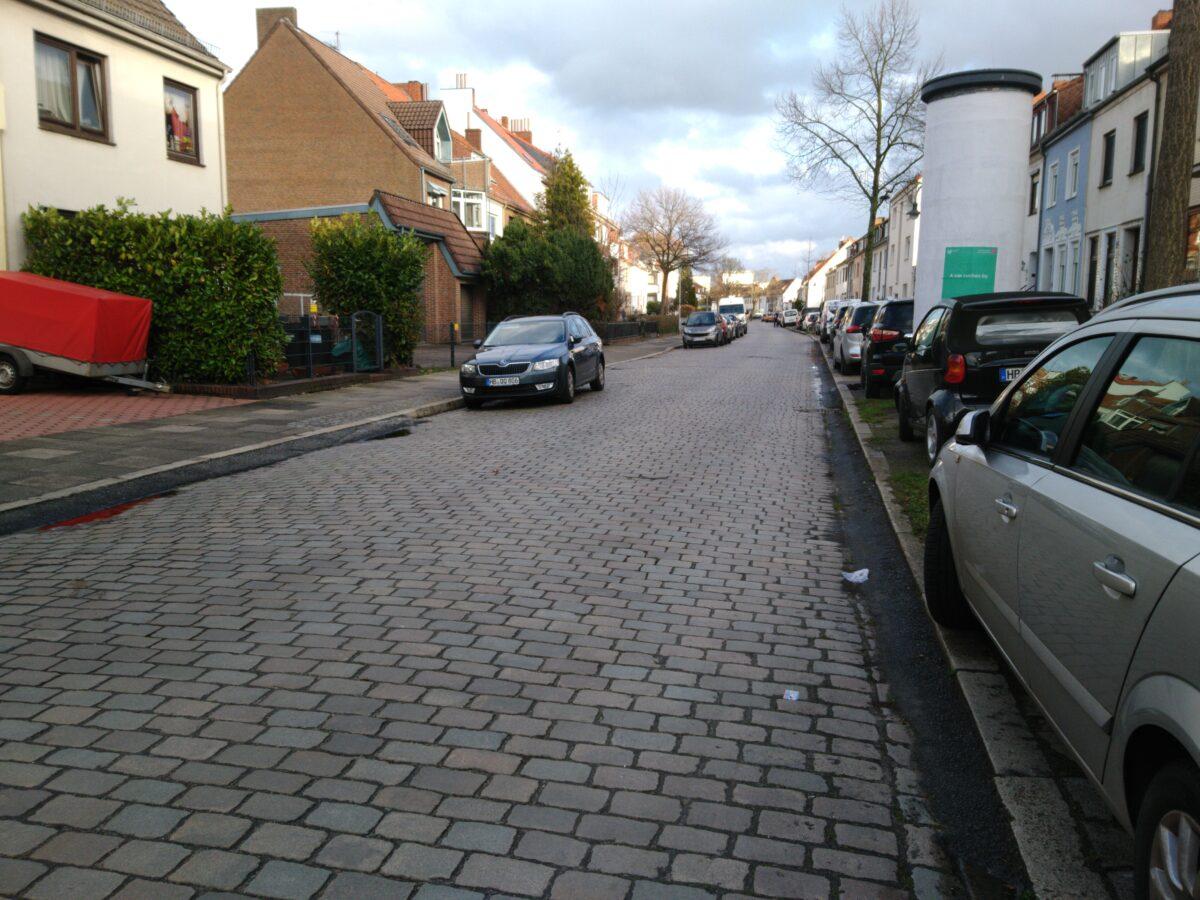Eine Kopfsteinpflasterstraße. Auf der Fahrbahn und dem Seitenstreifen parken Autos.