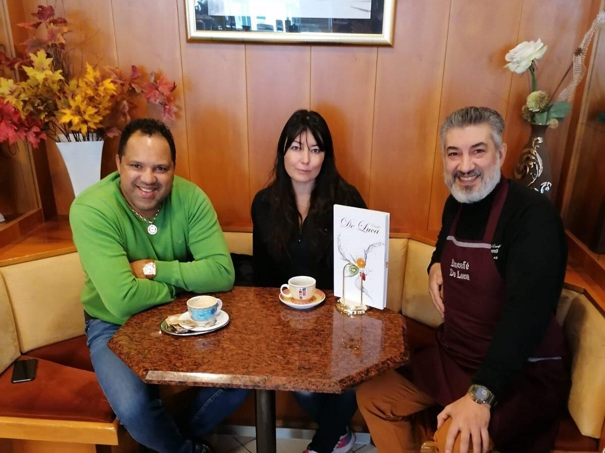 Drei Menschen sitzen an einem Eiscafé-Tisch.