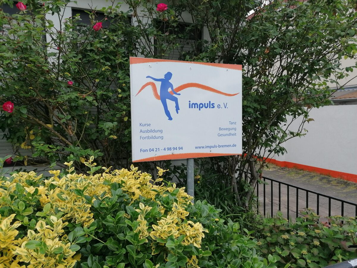 Ein Hinweisschild auf den Verein »Impuls« in einem Vorgarten.