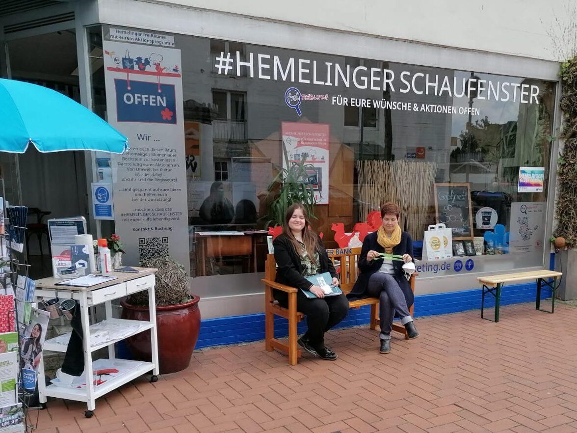 Zwei Frauen sitzen auf einer Bank vor dem Ladengeschäft »Hemelinger Schaufenster«