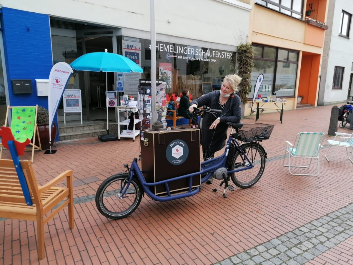 Eine Frau sitzt auf einem Lasten-Fahrrad vor dem Ladengeschäft »Hemelinger Schaufenster«.