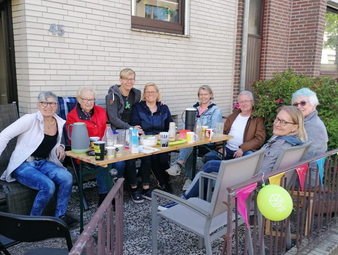 Acht Personen sitzen im Vorgarten eines Wohnhauses um einen Tisch