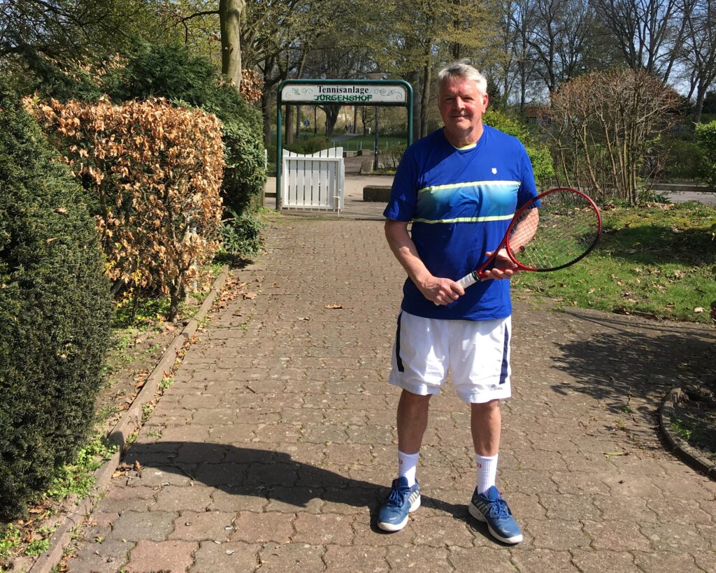Ein Mann in Sportkleidung steht auf dem Weg zum Eingang der Tennisanlage Jürgenshof.