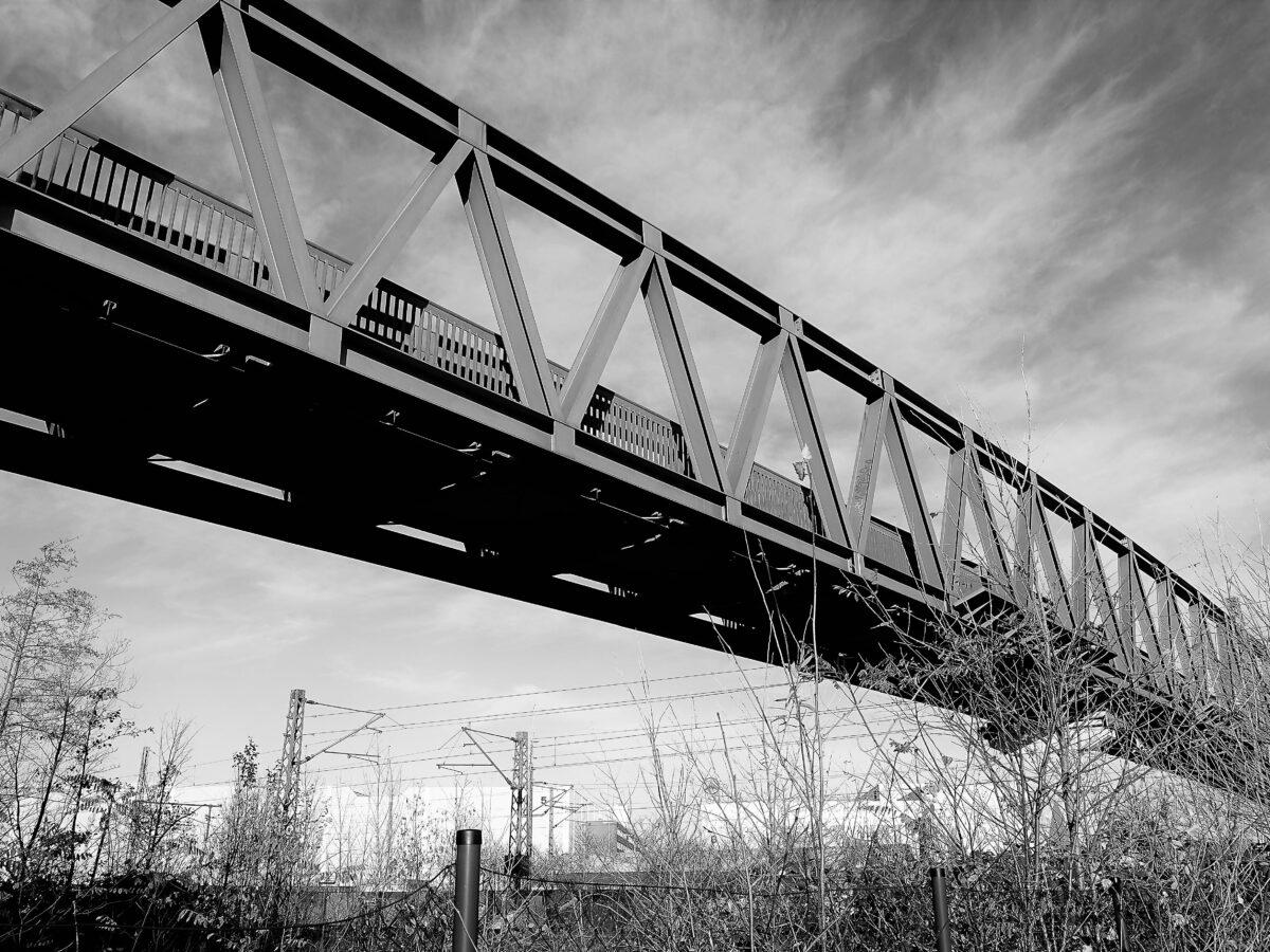 Eine Brücke über einer Eisenbahnlinie.