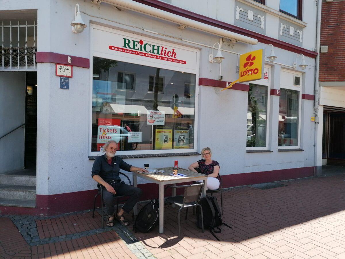 Zwei Menschen sitzen an einem Tisch vor einem Ladengeschäft.