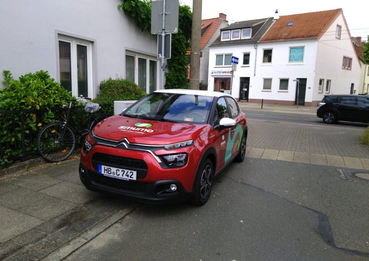 Ein rotes Auto des Anbieters Smumo steht am Rand einer Wohnstraße.