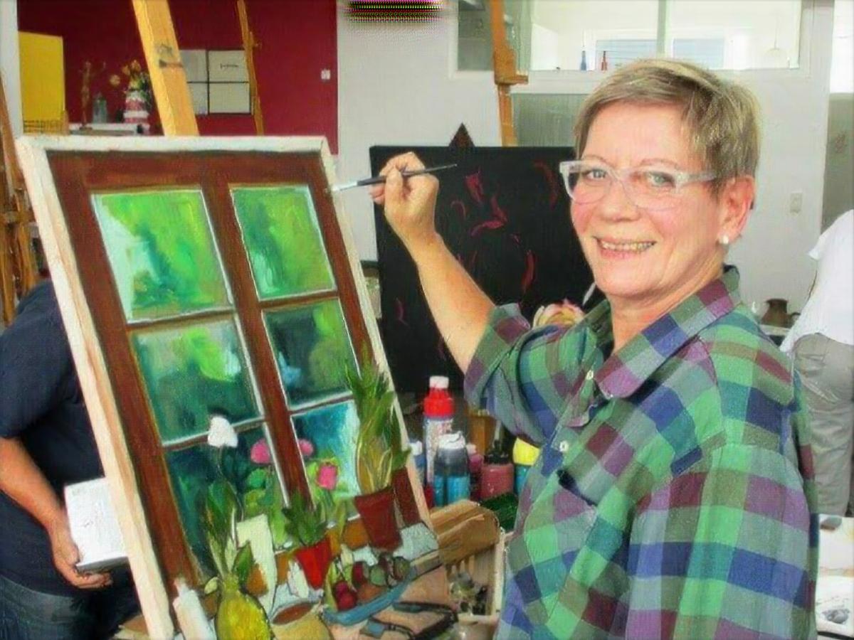 Eine Frau malt auf einer Leinwand ein Fenster mit Blumentöpfen davor