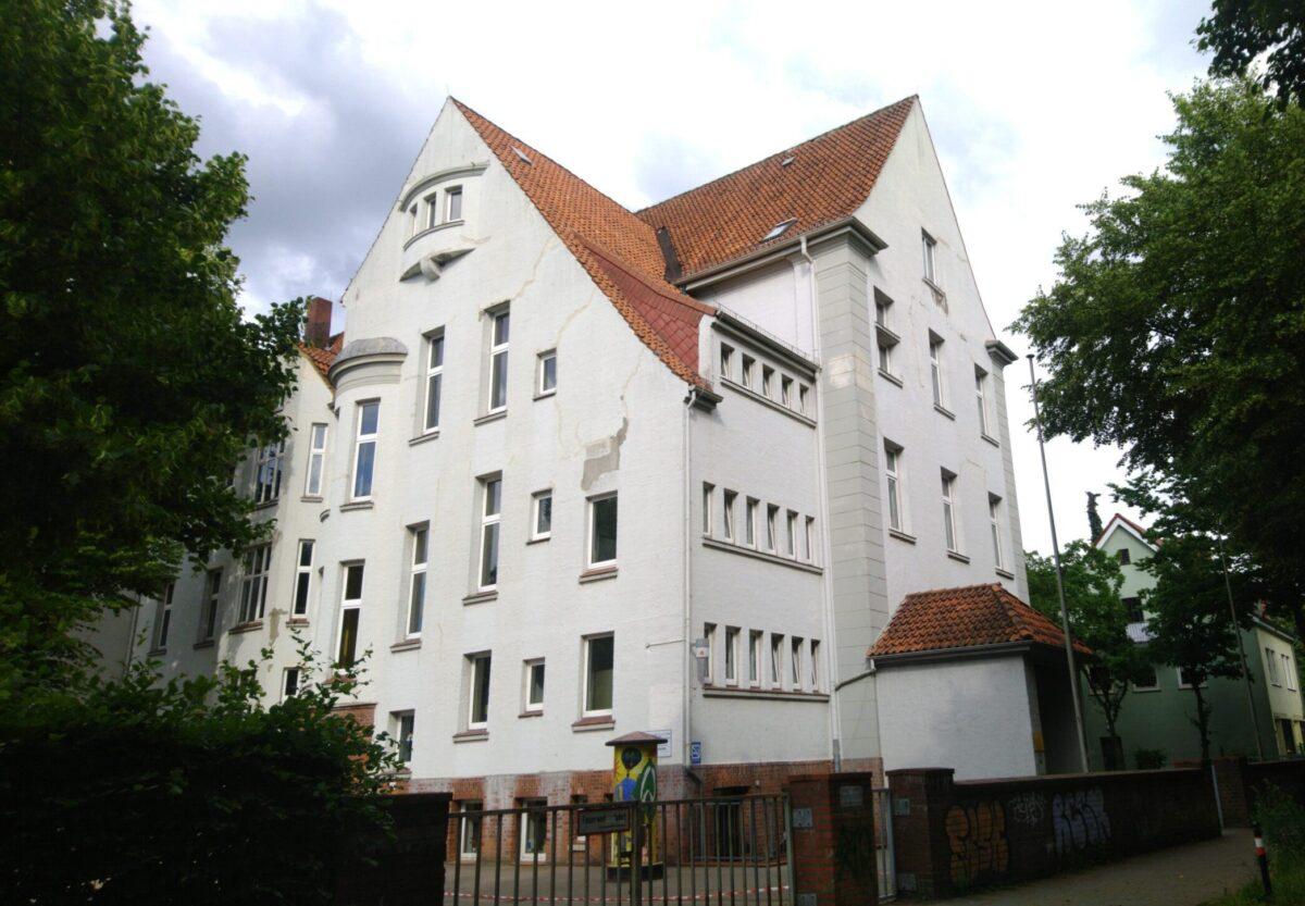 Das Schulgebäude am Alten Postweg. An der Fassade sind deutliche Risse zu sehen.